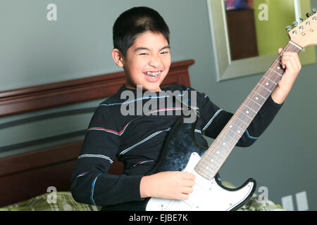 Asian boy play guitar in his bedroom - Stock Photo