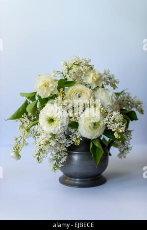 Spring flower arrangement with white ranunculus and lilac blossoms - Stock Photo