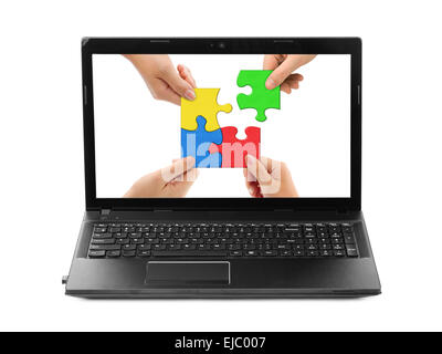 Hands and puzzle in computer notebook - Stock Photo