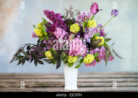 Spring floral bouquet with lilacs, tulips, Snowball bush, hellebore and euphorbia - Stock Photo