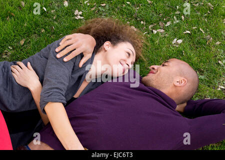 young couple lying in the grass together - Stock Photo