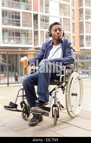 young wheelchair user relaxing with coffee. - Stock Photo