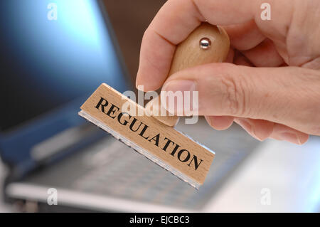 regulations marked on rubber stamp in hand - Stock Photo