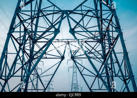 electricity transmission pylon silhouetted - Stock Photo