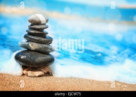 Stones pyramid on sand symbolizing zen - Stock Photo