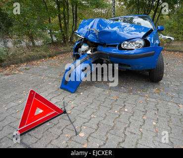 Damaged car with warning triangle - Stock Photo