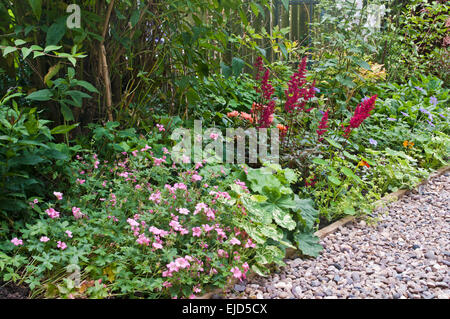 Detail of beautiful mixed herbaceous border with contrasting shrubs and flowers, next to pebble path, English garden, - Stock Photo