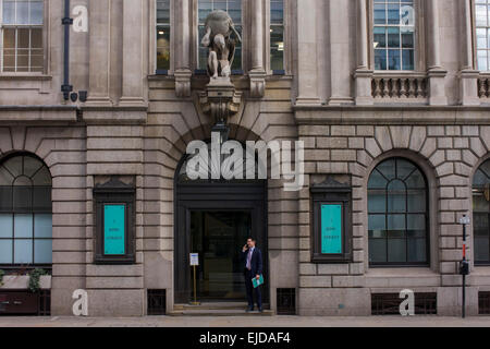A statue of Atlas is seemingly about to drop the globe onto a person standing below, in the doorway of a City institution. - Stock Photo