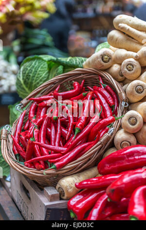 A basket of red chillies displayed on a vegetable stall against a backdrop of parsnips and cabbage - Stock Photo