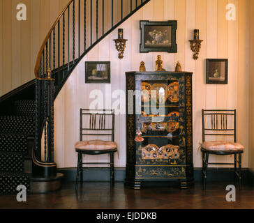 Antique painted glass front cabinet and chairs in eighties hall with sweeping staircase - Stock Photo