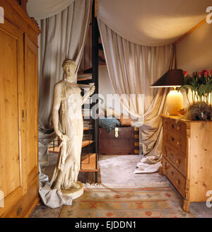 Classical marble statue in eighties hall with heavy cream drapes on ceiling and beside spiral staircase - Stock Photo