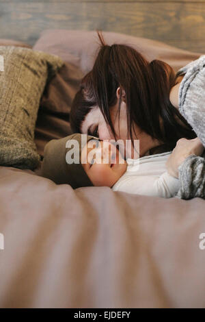 A mother and her young baby playing on a bed. - Stock Photo