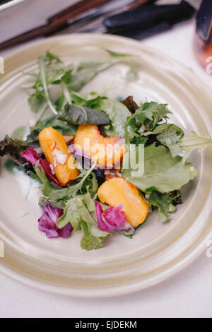 A plate of fresh salad leaves and slices of fresh peach fruit. - Stock Photo