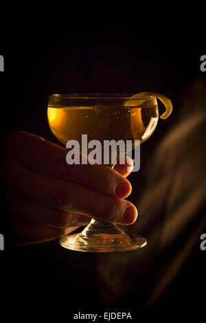 A woman's hand holding a cocktail glass. - Stock Photo