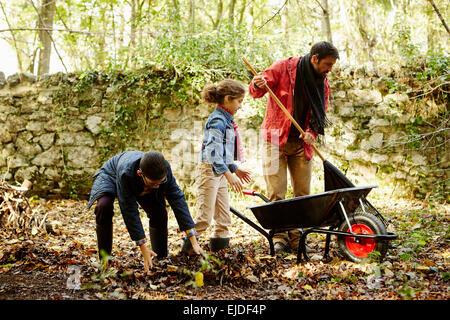 A family raking and scooping up leaves in autumn. - Stock Photo