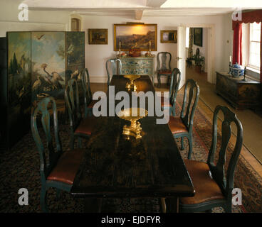 Antique oak table and painted chairs in retro dining room with painted folding screen - Stock Photo