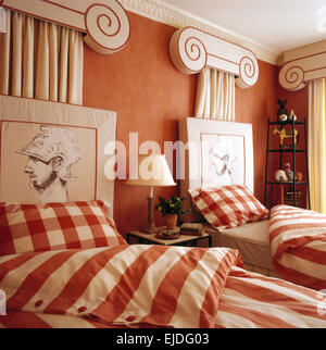 Eighties terracotta bedroom with twin beds with striped and checked bedlinen and painted neo-classical style headboards - Stock Photo