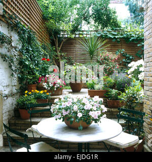 Table and chairs on patio in small town garden with colorful annuals in pots on steps and trellis fencing on the - Stock Photo