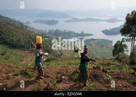 Female farmer with Lake Bunyonyi in the background. Uganda. - Stock Photo