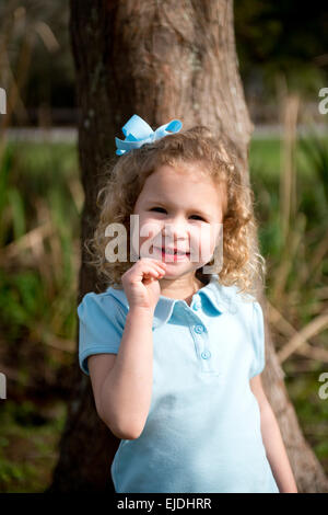 Young girl leaning against oak tree, portrait