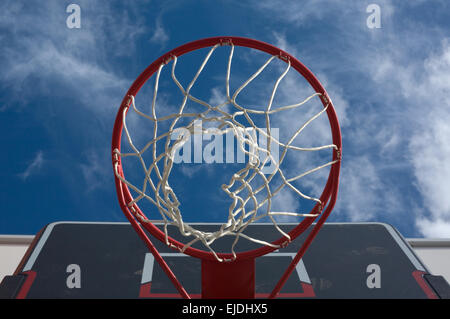 New basketball hoop from below against a cloudy sky - Stock Photo