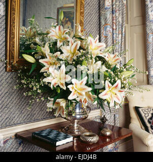 Close-up of white lilies in silver vase on small antique table - Stock Photo
