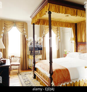 White drapes and linen on four poster bed in elegant ...