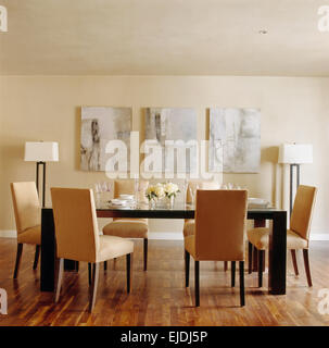 ... Suede Upholstered Chairs And Glass Topped Black Table In Modern Dining  Room With Abstract Paintings