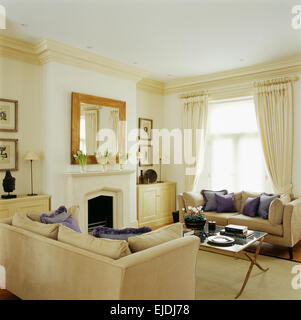 Mauve silk cushions on cream sofas in elegant townhouse sitting room with mirror above fireplace - Stock Photo