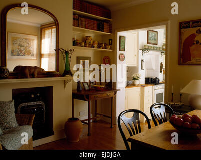 Victorian Mirror Above Fireplace In Nineties Dining Room With Doorway To Kitchen