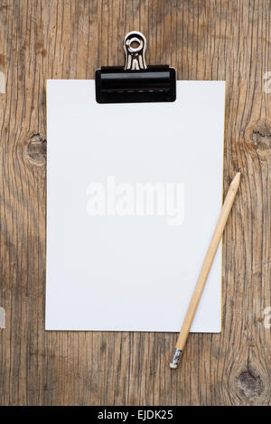 Clipboard and blank paper on wooden background - Stock Photo