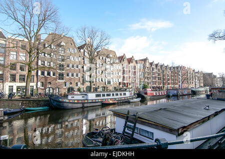 Brouwersgracht Canal in Amsterdam on a sunny day in winter.  A view of canal boats and barges & converted red brick - Stock Photo