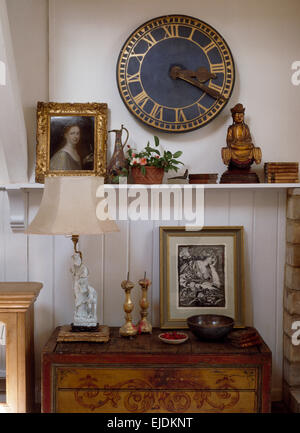 Circular clock on wall above shelf with small Buddha and gilt framed picture above lamp on painted chest - Stock Photo