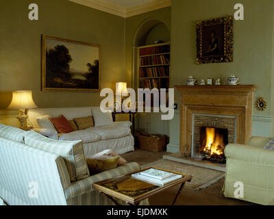 Comfortable sofas around fireplace with lighted fire in traditional style eighties sitting room - Stock Photo