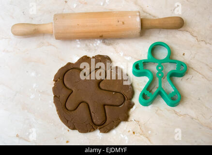 Rolling pin on kitchen counter with rolled out dough and cut out of gingerbread man shape - Stock Photo