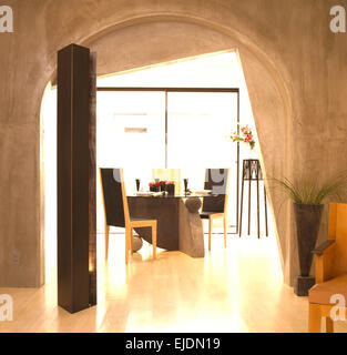 Concrete walls and polished floor in dining area with arched doorway and tall speaker in late eighties Californian - Stock Photo