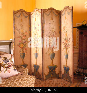 Painted antique folding screen in country house bedroom - Stock Photo