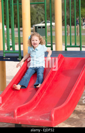 Young girl goes down slide at park playground - Stock Photo