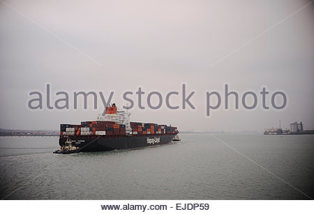 The German flagged container ship 'Seoul Express' travels up Southampton Water during a murky winter's day. Hampshire, UK.