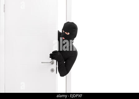 Studio shot of a stealthy thief breaking into a room through a door and carefully looking around isolated on white - Stock Photo