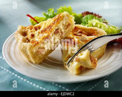 quiche Loraine slices with salad - Stock Photo