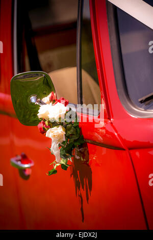 A bright red VW camper bus prepared for a wedding. - Stock Photo