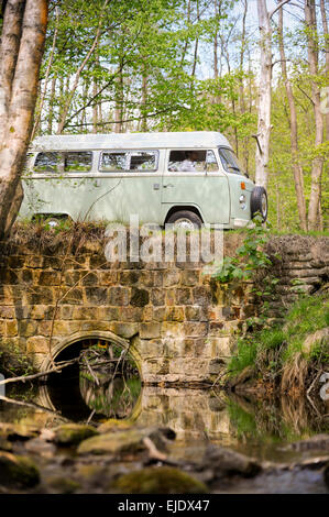 Volkswagen Camper crossing a bridge over a stream on the Ashdown Forest in East Sussex UK. Stock Photo
