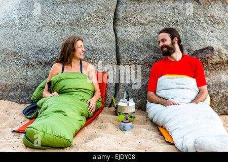 Man and a woman on the beach in sleeping bags laughing - Stock Photo