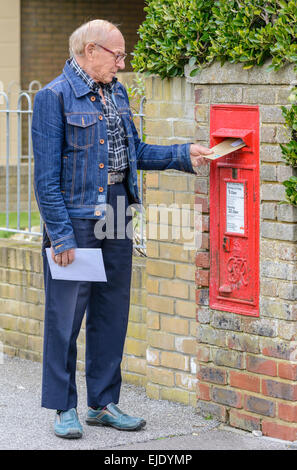 Elderly man posting a letter in a Royal Mail wall mounted letter box, in England, UK. - Stock Photo