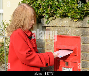 Middle aged woman posting a letter in a Royal Mail wall mounted letter box, in England, UK. - Stock Photo