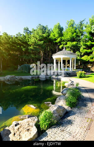 White arbour near beautiful lake in park - Stock Photo