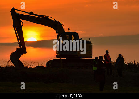 Mechanical digger and workers silhouetted again the evening sun, Londonderry, Derry, Northern Ireland - Stock Photo