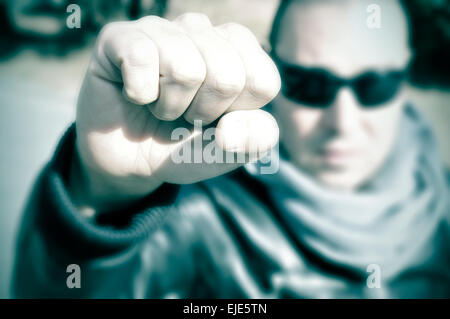 closeup of a young man in a protest raising his fist and with his face blurred, with a filter effect - Stock Photo