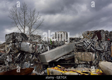 Heap of cubes of crushed recycled scrap metal junk with clouds and tree in Spring Toronto - Stock Photo